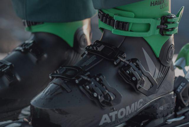 Atomic black ski boots on the snow.
