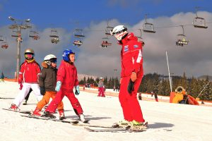 Ski instructor teaching kids beginners