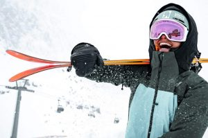 A woman carries Blizzard skis.