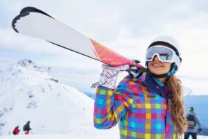 Top all women's skis, woman holding skis.